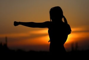 Femme qui s'entraine sur fond de coucher de soleil