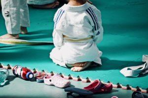 Enfant assis en tailleur de dos sur tatamis